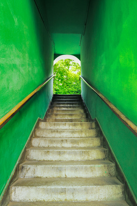 Old grungy stairs with handrails on green wall