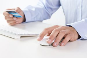 Male hand using computer and credit card for online payment