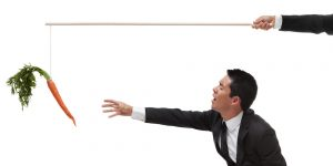 Exhausted Businessman reaching for a carrot on the end of a stick