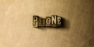 PHONE – close-up of grungy vintage typeset word on metal backdrop